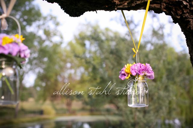 Mason jars with flowers hung from ceremony tree